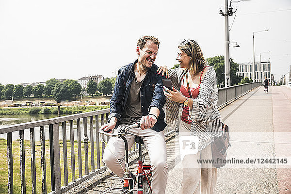 Happy couple with bicycle and cell phone crossing a bridge