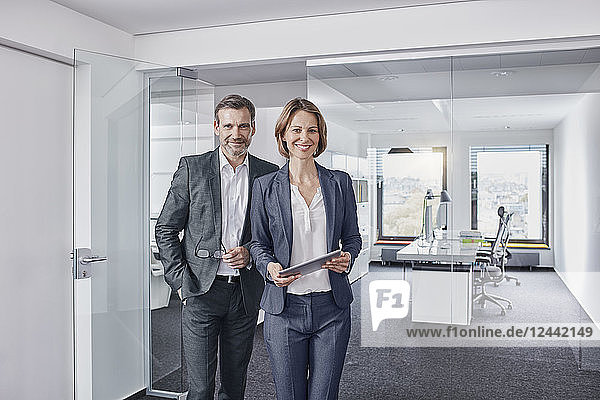 Portrait of smiling businessman and businesswoman with tablet in office