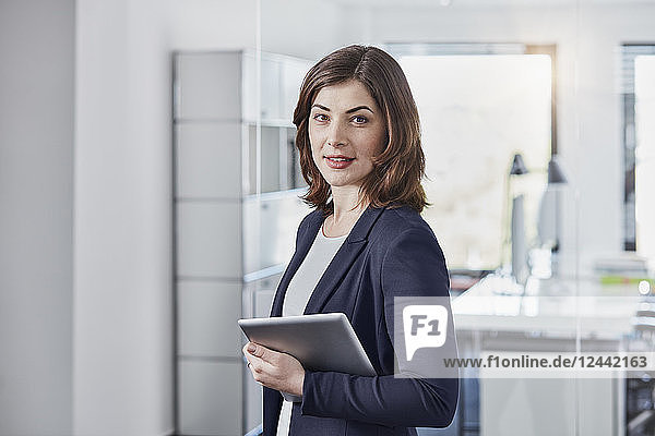 Portrait of smiling young businesswoman with tablet in office