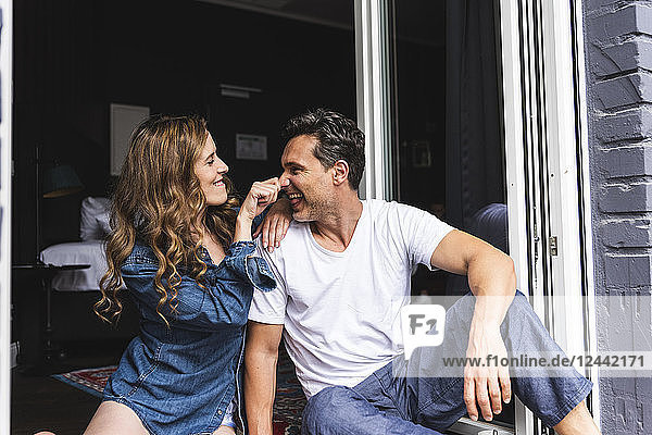 Playful couple in nightwear at home sitting at French window