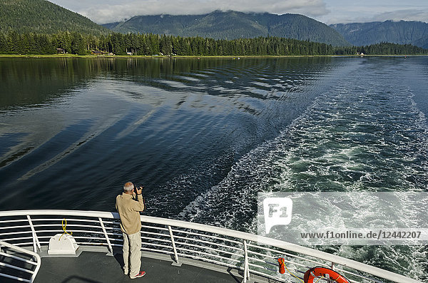 Tourist photographing Wrangell Narrows looking North toward Petersburg from stern of Alaska State Ferry  Southeast Alaska; Alaska  United States of America