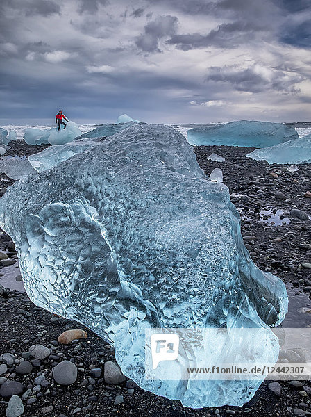 Blue ice on the shore of Jokulsarlon with a man standing on an iceberg in the distance  South coast; Iceland