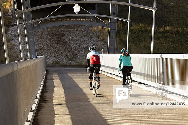 Two Cyclists Riding Across A Concrete Bridge On A Fall Evening; Edmonton  Alberta  Canada
