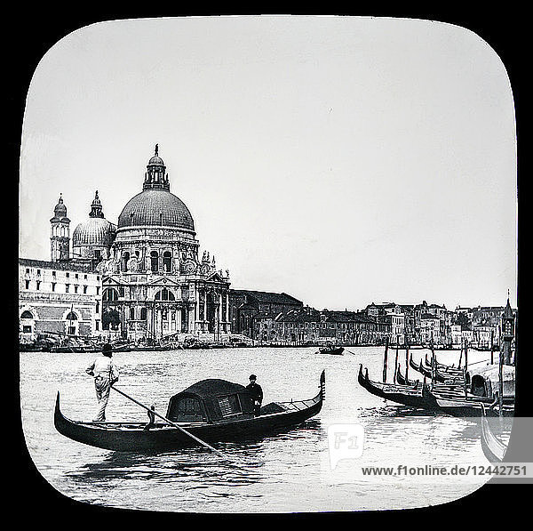 Gondola and gondolier  Grand Canal and Salute Church  Venice circa 1900 on a magic lantern slide. Photographed by Joseph John William in 1888; Venice  Italy