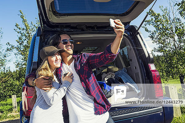 Young couple at their vehicle with the back open taking a self-portrait with their cell phone  Edmonton  Alberta  Canada