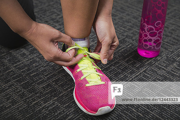 Woman tying a green shoelace on a pink running shoe while working out  Spruce Grove  Alberta  Canada