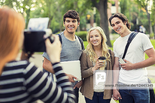 A young woman takes a picture of three friends on a university campus  Edmonton  Alberta  Canada