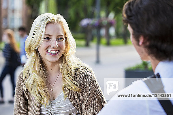A beautiful young woman talking to her boyfriend in the university campus  Edmonton  Alberta  Canada