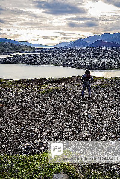 A female tourist poses on the edge of a hilltop overlooking a vast river valley in Western Iceland  Iceland