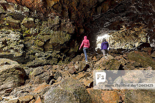 Two female tourists hiking through the lava tube caves  Iceland