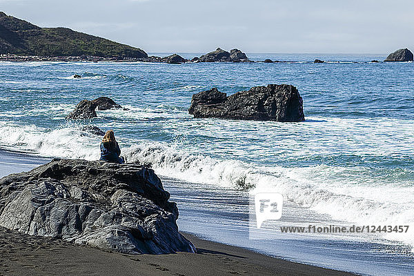 A woman sits on a rock on the beach watching the waves coming ashore along the rocky California coast  Crescent City  California  United States of America