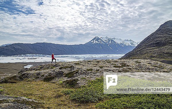 A female hiker walks along the edge of a hill on the trail above a glacier lake and mountain viewpoint in Southern Iceland  Vatnajokull National Park  Iceland