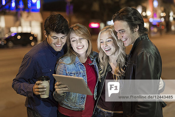 A group of four friends huddle together on a sidewalk looking at a tablet as the glow from the screen lights up their faces  Edmonton  Alberta  Canada