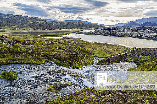 A small river runs through a valley in Western Iceland towards the large river below and the distant richly colored volcanic peaks in the distance  Iceland