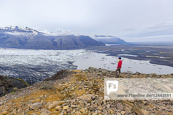 A female hiker in warm clothing for the elements stands on the edge of moutain cliff overlooking the glacier lake and valley views of Vatnajokull National Park  Iceland