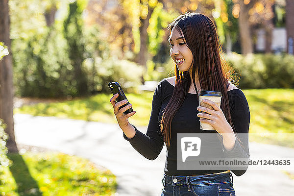A young Chinese International student stands holding a coffee cup and using her smart phone on a university campus  Edmonton  Alberta  Canada