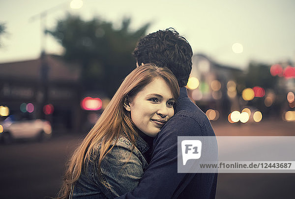 A young couple stands embracing on a sidewalk in a popular area at dusk  Edmonton  Alberta  Canada