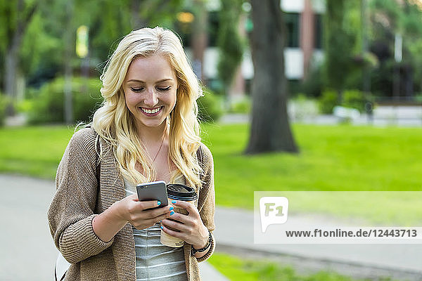 A beautiful young woman with long blond hair holding a coffee cup and texting on her smart phone while walking in a university campus  Edmonton  Alberta  Canada