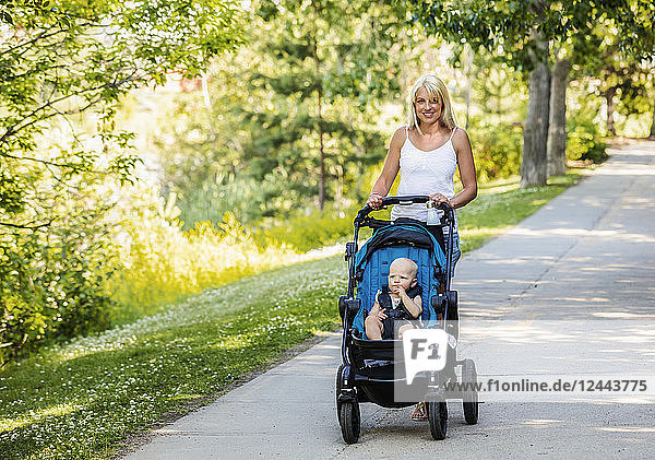 A beautiful young mother taking her baby daughter out for a walk using a stroller in a park with a lake on a warm sunny day  Edmonton  Alberta  Canada