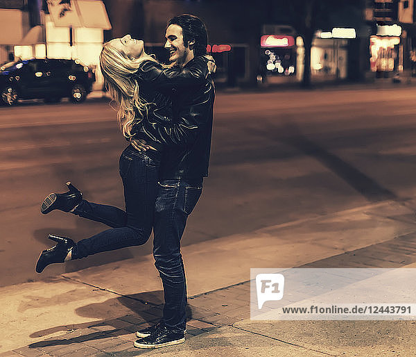 A young couple wearing black leather jackets being playful on a city sidewalk at night  Edmonton  Alberta  Canada