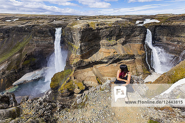 A young asian female hiker poses for a portrait on the edge of a stunning double waterfall valley landscape known as Haifoss  Iceland