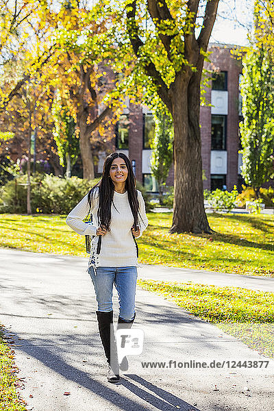 A young female university student of Lebanese ethnicity walking on a path on campus with a backpack  Edmonton  Alberta  Canada