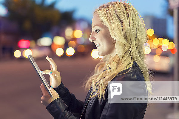 A young woman with blond hair uses a tablet along a street at dusk with the glowing screen illuminating her face  Edmonton  Alberta  Canada