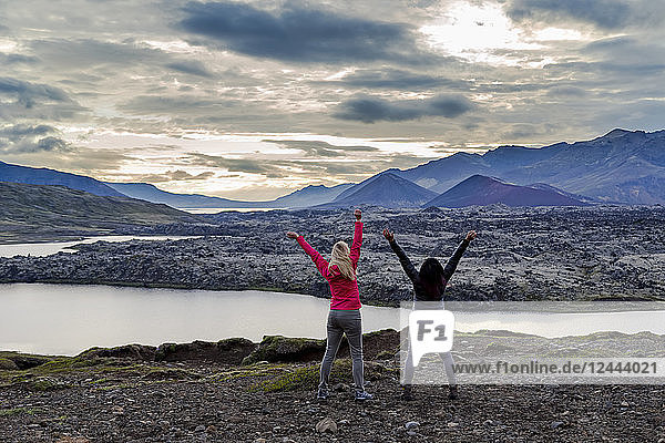 Two female travellers celebrate their hike and embrace the excitement of this beautiful nature viewpoint in Western Iceland  Iceland