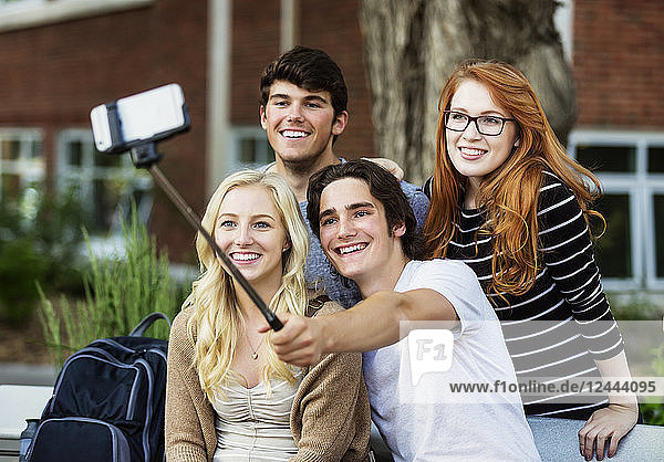 A group of four friends sitting on a bench taking a self-portrait with a smart phone using a selfie stick on a university campus  Edmonton  Alberta  Canada