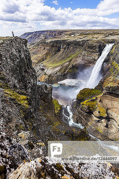 A female hiker poses on the edge of a high cliff over the waterfall valley of Haifoss,  Iceland