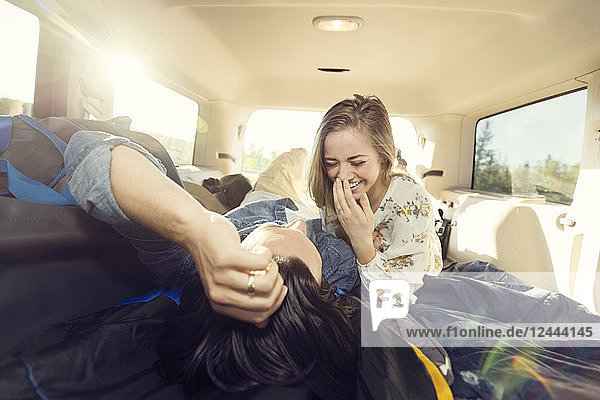 A young couple lays in the back of their vehicle during a road trip talking and laughing together  Edmonton  Alberta  Canada