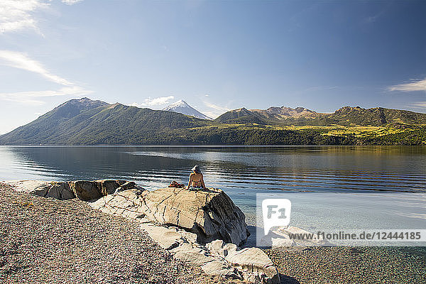 A woman basking in the sun on the shore of a lake with a snow-capped volcano in the distance  Neuquen  Argentina