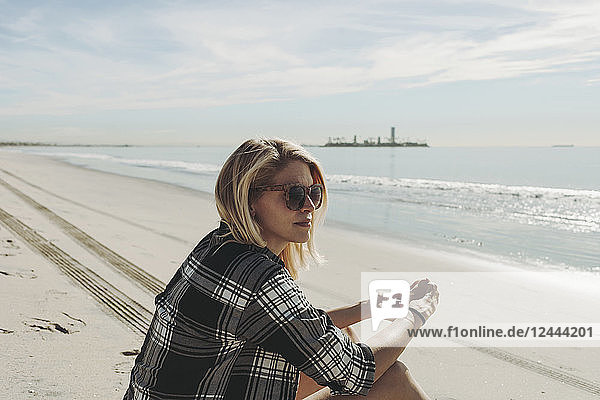 A woman sits on a beach looking out to the water; Long Beach  California  United States of America