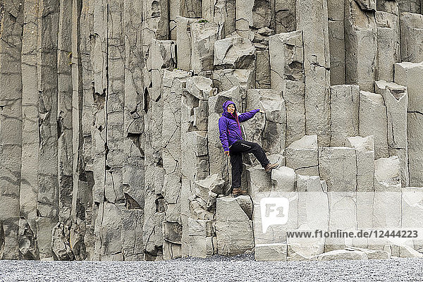 A female tourist poses on the basalt rock columns on the Reynisfjara beach in Southern Iceland  Iceland