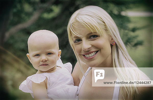 A beautiful young mother with long blonde hair enjoying quality time with her cute baby daughter in a city park on a summer day and posing for the camera  Edmonton  Alberta  Canada
