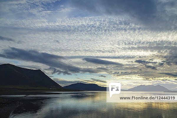 Sunset and cloudy skies over a remote ocean inlet in Western Iceland on the Snaefellsnes Peninsula  Iceland