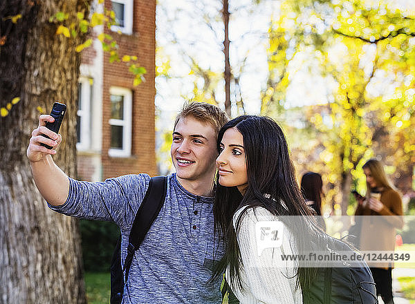 A couple who are university students posing for a self-portrait with a smart phone with a small group of friends in the background  Edmonton  Alberta  Canada