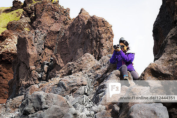 A tourist sits on the top of a rock formation to take a higher photo of the landscape,  Iceland