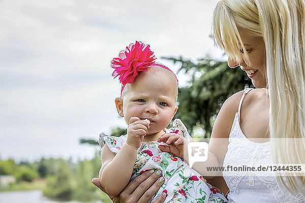 A beautiful young mother with long blonde hair enjoying quality time with her cute baby daughter in a city park on a summer day  Edmonton  Alberta  Canada