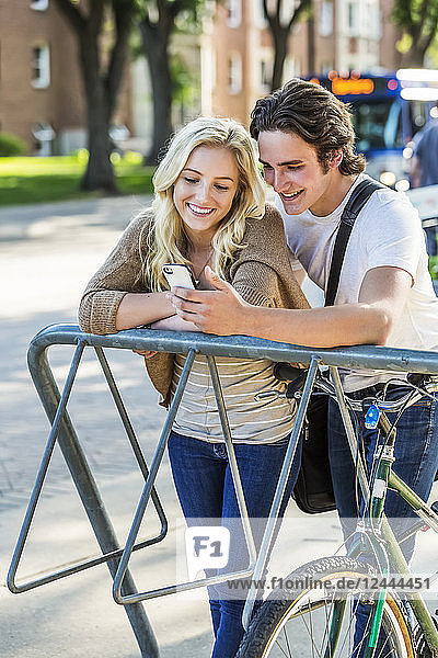 A young couple stands together at a bike rack on the university campus looking at a smart phone  Edmonton  Alberta  Canada