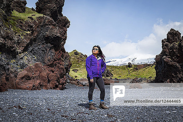An Asian female tourist poses for a portrait on the black sand beach next to a rock formation in Western Iceland  Snaefellsnes peninsula  Iceland