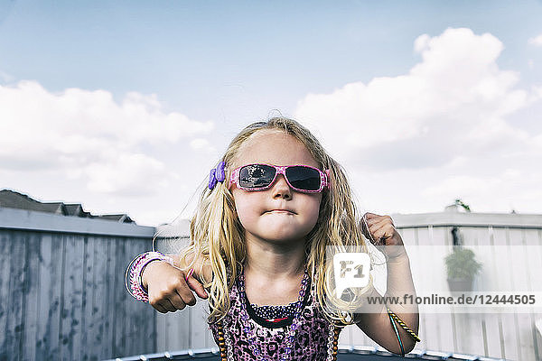A young girl all dressed up with blond curly hair  sunglasses and jewelry standing on a trampoline in the backyard and showing off; Spruce Grove  Alberta  Canada