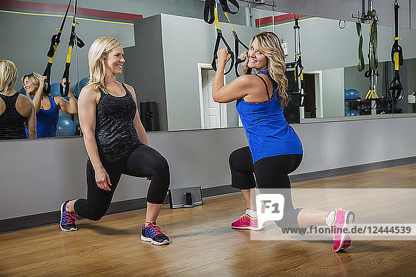 A personal trainer coaching her client while she works out in a gym using straps to tone her muscles  Spruce Grove  Alberta  Canada