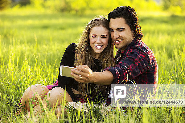 Young couple sit on the grass in a park posing for a self-portrait with their cell phone  Edmonton  Alberta  Canada