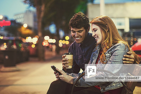 A young couple sits on a bench along a popular street at dusk looking at a smart phone  Edmonton  Alberta  Canada