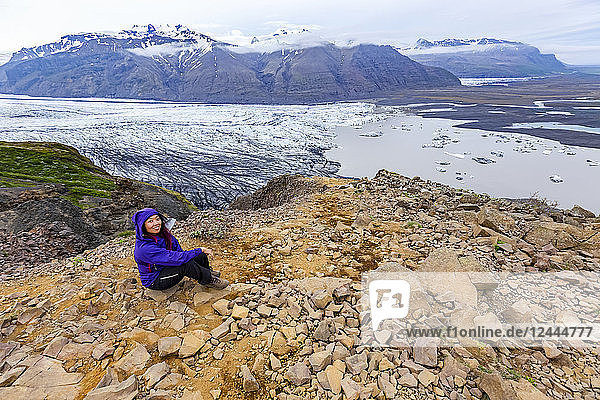 A female hiker in warm clothing poses on a mountain top overlooking the glacier lake and valley below at Vatnajokull National Park  Iceland
