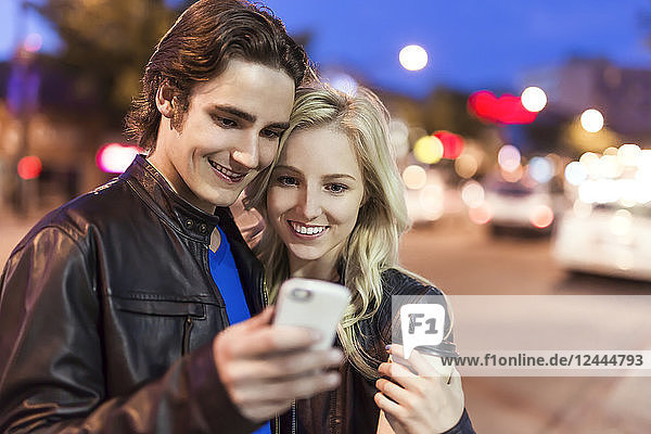 A young couple use a smart phone along a street at dusk  Edmonton  Alberta  Canada