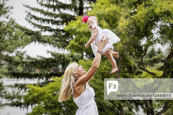 A beautiful young mother with long blonde hair enjoying quality time with her cute baby daughter and tossing her in the air in a city park on a summer day  Edmonton  Alberta  Canada