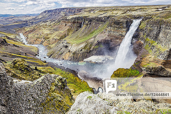 A high viewpoint of one of the waterfalls and rivers in the Haifoss valley with stunning cliffs  natural colors and rock formations  Iceland