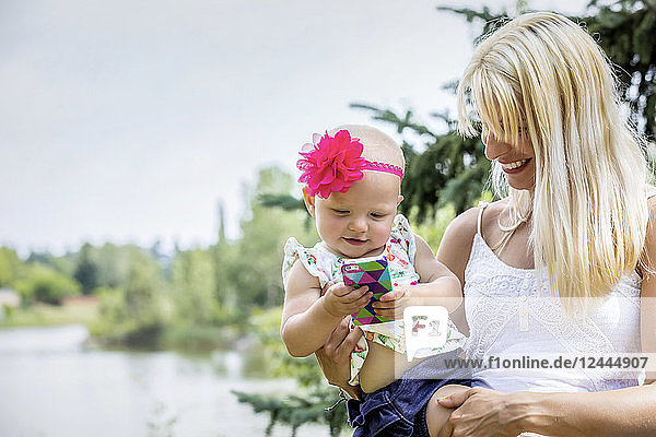 A beautiful young mother with long blonde hair enjoying quality time with her cute baby daughter who is amused with a smart phone in a city park on a summer day  Edmonton  Alberta  Canada